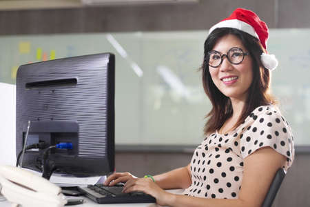 office girl smiling, an officer wear Santa hat working and smiling. photo