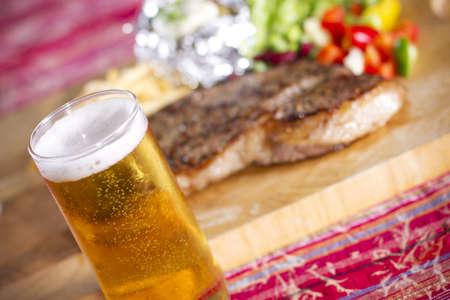 ステーキと食事、牛ステーキ、ビールをテーブルに設定されて、 写真素材