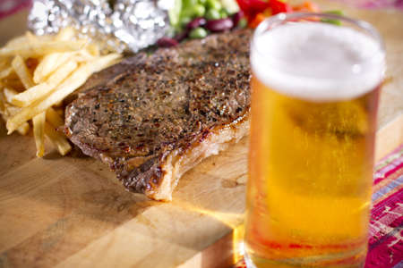 steak meal, set of beef steak and beer on the table. Stock Photo