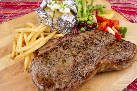 sirloin steak, set of steak with salad, fries and baked potato. photo