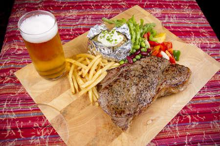 お食事セット、ステーキとサラダ、フライド ポテト、ベークド ポテトとビールのセット。