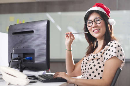 Santa office working, Asian Santa lady smiling working at office. photo