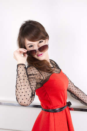 charming red, female model in red dress pose with sunglasses.