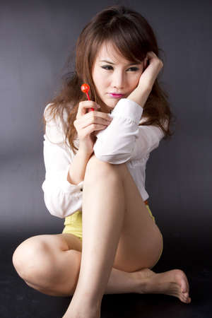 sexy candy girl, female model pose cute action with red candy. Stock Photo - 12004737