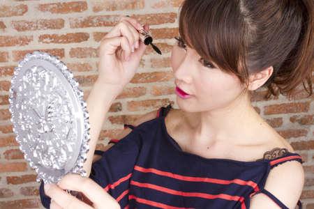 メイクアップ、女性モデルを使用して黒マスカラーまつげを置きます。