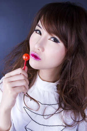 candy kiss, female model pose cute action with red candy. photo