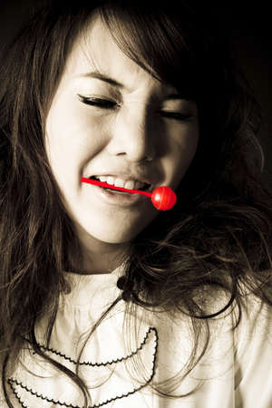 bite candy, female model pose cute action with red candy. photo
