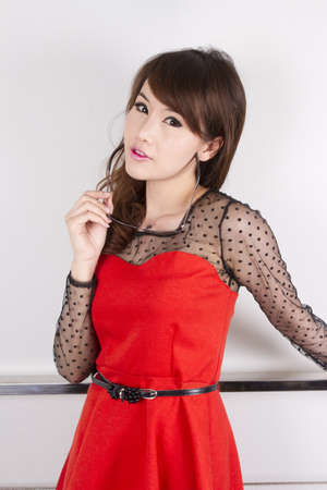 pretty red, female model in red dress standing pose.