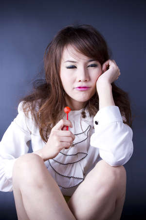 boring girl, female model pose bored with red candy. photo