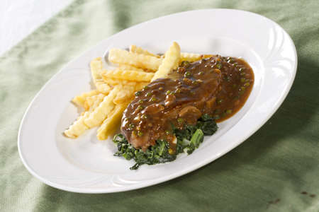 rib eye: rib eye steak, beef steak with brown sauce spinach and french fries
