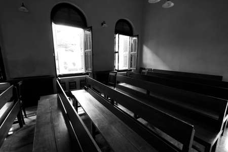 bible altar: church row, black and white church row seat with sunlight Editorial