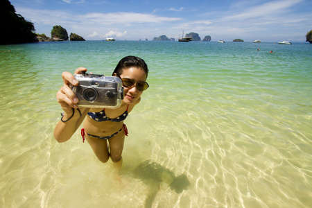 vacation girl, live Asian girl hold camera on the bikini beach photo