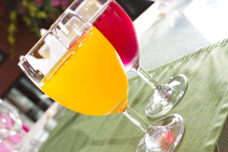 pure juices, two glasses of orange and strawberry juices on table photo