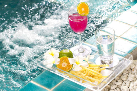 pool bar: snack break, tray of snacks, fruit juice and water by the pool Stock Photo