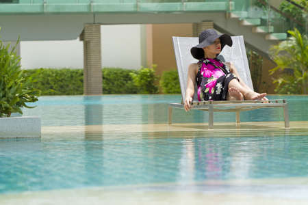 Woman relaxation, Asian woman wear pink sarong relaxing at resort pool photo