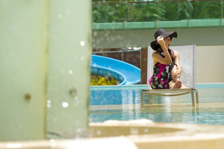 Resort relaxation, Asian woman wear pink sarong relaxing at resort pool photo