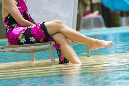 Pool resort, Asian woman in pink flower towel fabric relaxing in pool resort photo
