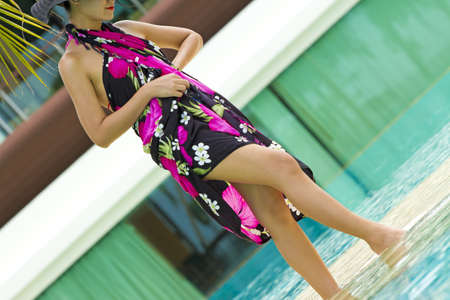 Woman in the pool, asian woman in pink flower paint sarong walking in the pool photo