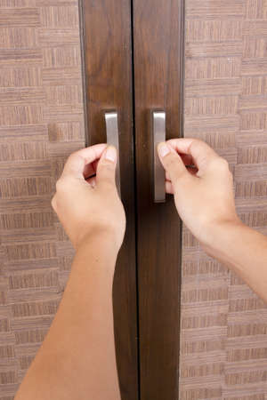 to open closet door, female hands opening closet door Stock Photo - 14184460