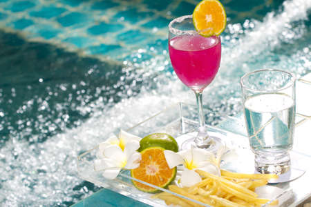 tea break, pink cocktail decorated with orange by the Jacuzzi pool photo