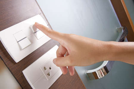 electricity supply: turn on switch, female hand turn on white electricity switch