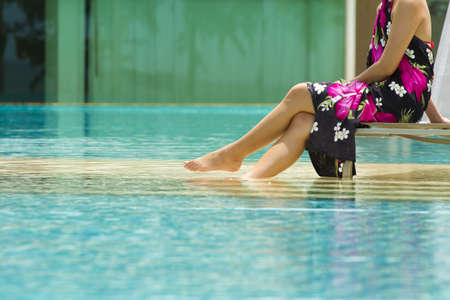 modern pool, asian woman in pink flower paint sarong sit by the pool photo