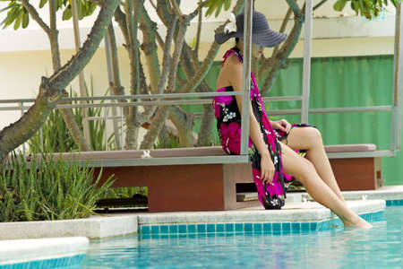 by the pool, asian woman in pink flower paint sarong sit by the pool photo