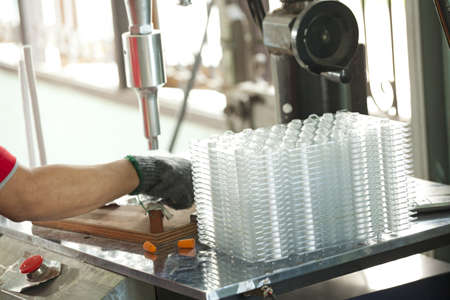 plastic container: molding plastic line, worker in plastic factory working on ultrasonic molding Stock Photo