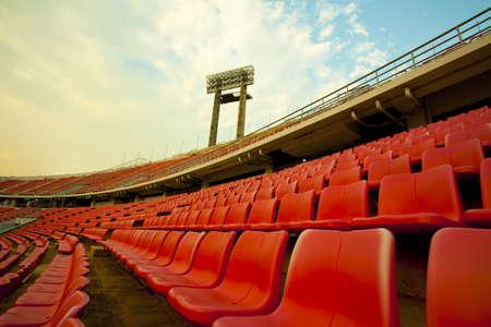 stadium, red seats on stadium steps bleacher with spot light pole
