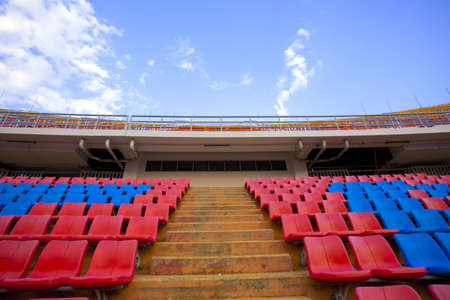 stadium aisle, red  and blue seats on stadium steps isle up bright sky