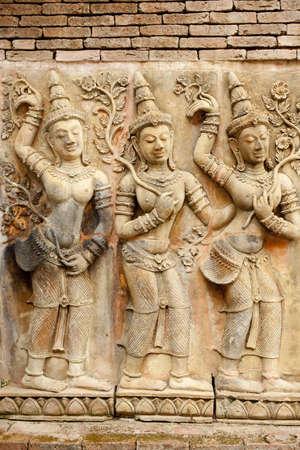 antique woman: antiguo arte de la pared, decoraci�n de la pared arte antiguo en la mujer mantenga la hoja y el baile en la cultura tailandesa Foto de archivo