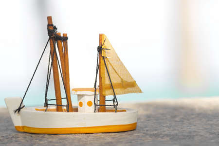 topsail: toy sailboat, yellow mini toy sailboat with water background