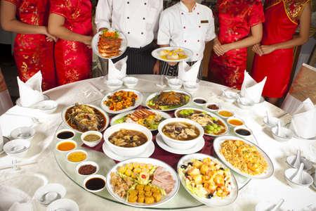 plat chinois: La nourriture chinoise, table arrondie pleine de nourriture chinoise avec le chef et cheongsam serveuse derri�re Banque d'images