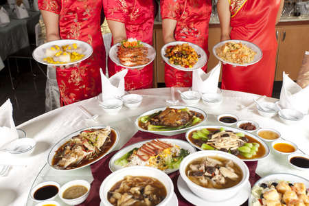 Chinese food, full rounded table of Chinese food with waitress behind Stock Photo