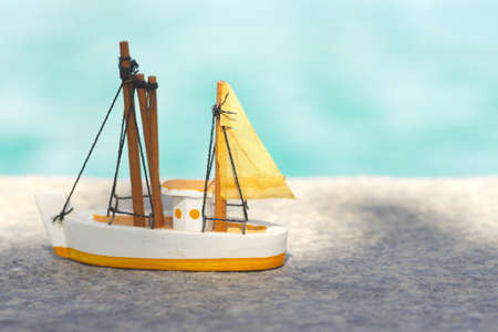 toy sailboat, yellow wooden miniature toy sailboat by the pool photo