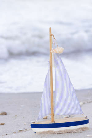 topsail: wood sailboat, blue wooden canvas sailboat on the sand beach