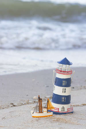 light house, blue light house and yellow ship toy on the sand beach photo