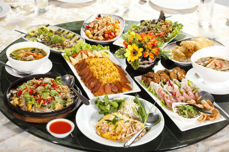 chinese cuisine: mixed food, full rounded table of Chinese Thai food, duck and sauce Stock Photo