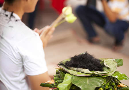 ordain: to be ordained, pile of cut hair on lotus leaf show a man to be ordainted