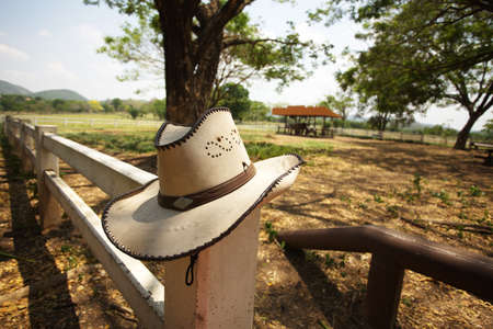 ranches: cowboy hat, light brown cowboy hat hanging on farm fence Stock Photo