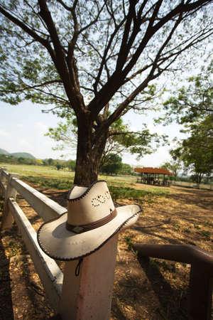 rodeo americano: sombrero de vaquero, sombrero de vaquero luz marr�n colgando en la cerca de la granja