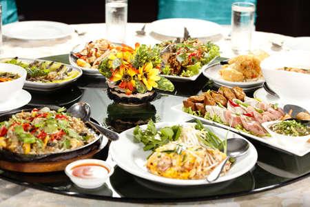 lunchen: maaltijd, volle ronde tafel met kleurrijke eten in restaurant