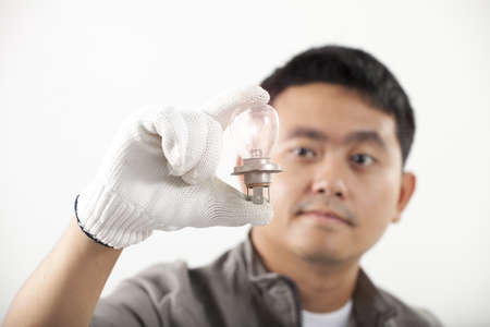 light bulb, Asian engineer man hold lighting bulb in his hand photo