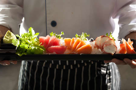 sashimi, Male model in chef uniform holding a dish of Japanese Sashimi