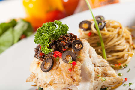 fish steak, decorated fish steak with pan fried spinach side with spaghetti on dish photo