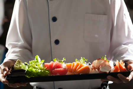 sashimi, Male model in chef uniform holding a dish of Japanese Sashimi