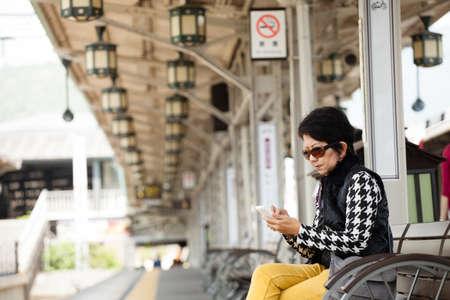 Travel Japan, Senior woman tourist use smart phone at train station, Arashiyama, Kyoto, Japan photo