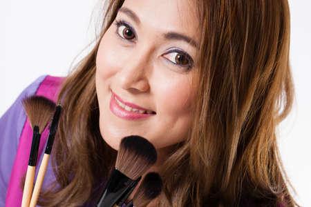 Make-up Artist, female Thai beautiful make up artist smile and holding brushes photo