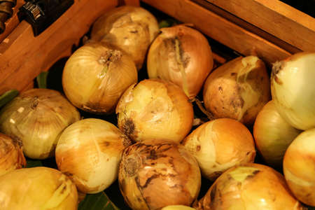 close up of onions in a basket: white onion, fresh white onion put in wood box at the market Stock Photo