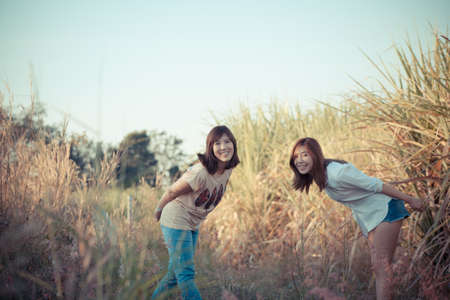 sugar cane farm: sisters in nature, female Asian sisters happy together in sugar cane farm